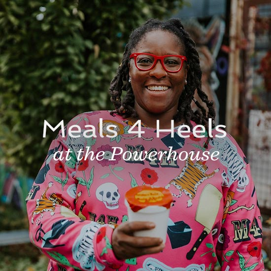 "Nikeisah Newton wearing red framed glasses and a a bright pink patterned sweater and holding a cup of coffee smiles at the camera. The text ""Meals 4 Heels at the Powerhouse"" is overlaid on the picture."