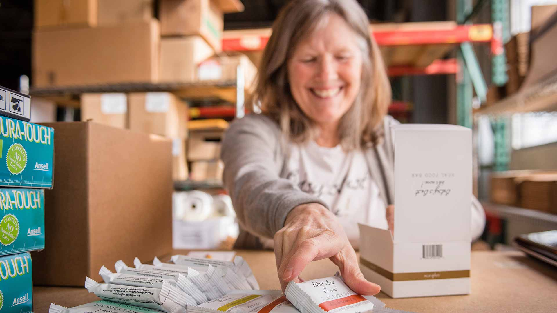 smiling woman in a work room boxes up energy bars