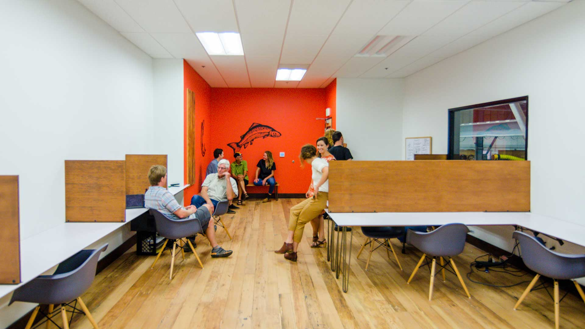 several people sit talking on chairs and tables in open office space
